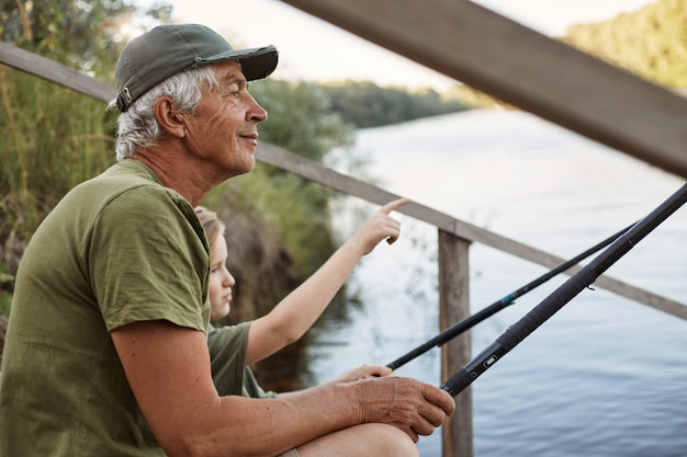 Senior man with his grandson sitting on wooden pontoon with fishing rods in hands, enjoying beautiful nature, little boy pointing at something with his finger.