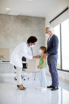 アフリカ系アメリカ人の女性医師による小児科医の検査で彼の小さな孫娘と年配の男性