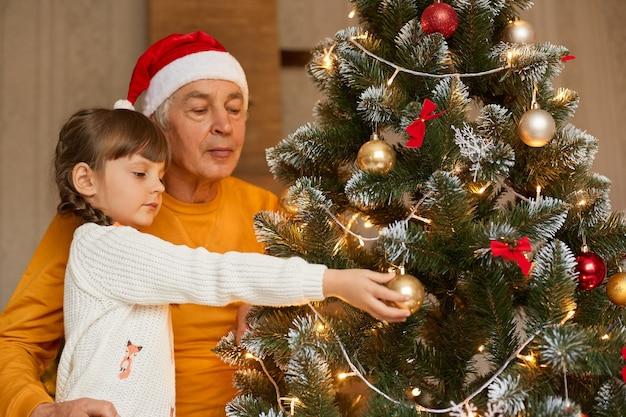 自宅でクリスマスツリーを飾る彼の小さな孫娘と年配の男性