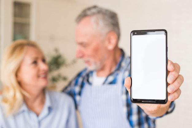 Senior man with his wife showing mobile phone toward camera holding in hand