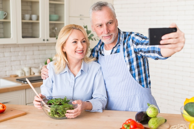Senior man with his wife with green salad bowl taking selfie on mobile phone in the kitchen