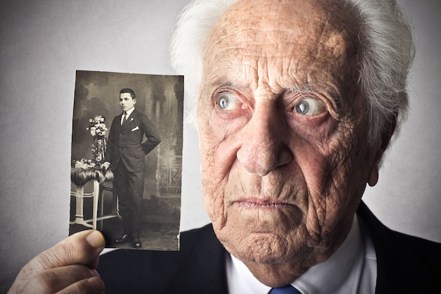 Senior man with his young photograph