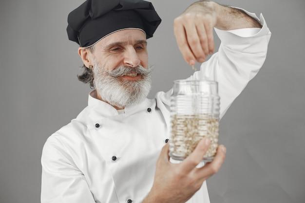 オートミールの瓶を持つ年配の男性。