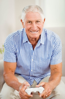 Senior man with joystick looking at camera and smiling in living room