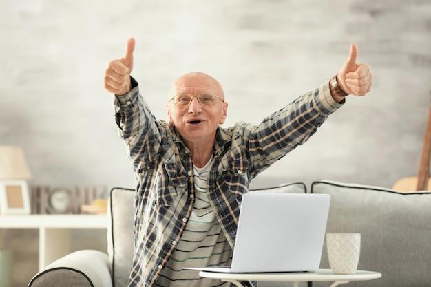 自宅でラップトップを持つ年配の男性