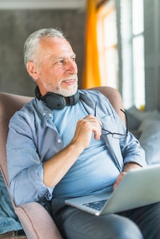 Senior man with laptop sitting on armchair looking away