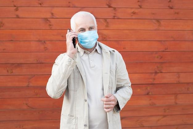 電話を使用して医療フェイスマスクを持つシニア男。感染を止める、男は感染症やインフルエンザに対する保護マスクを着用します。医療コンセプト。