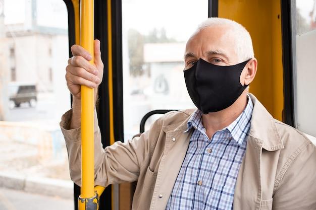 公共交通機関の医療マスクを持つ年配の男性。ウイルス防止