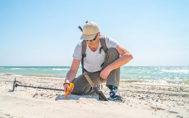 海の近くの晴れた日に砂の中で金属探知機とシャベル検索ジュエリーを持つ年配の男性。