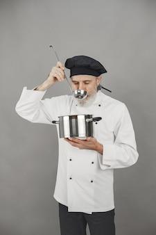 Uomo anziano con padella in metallo. chef con un cappello nero.