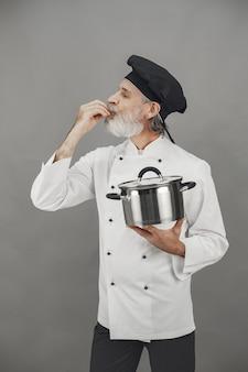 金属鍋を持つ年配の男性。黒い帽子をかぶったシェフ。ビジネスへの専門的なアプローチ。