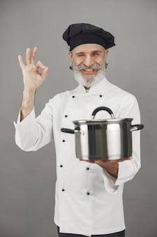 Старший мужчина с металлической сковородой. повар в черной шляпе.