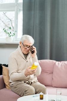 ソファに座って、彼の手で薬の瓶を見て、それらを取る方法について彼の医者と相談している携帯電話を持つ年配の男性