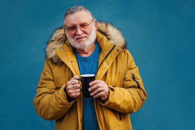 熱い飲み物のマグカップを持つ年配の男性。ホットドリンクを楽しんでいるスタイリッシュなアウターウェアの嬉しい老人