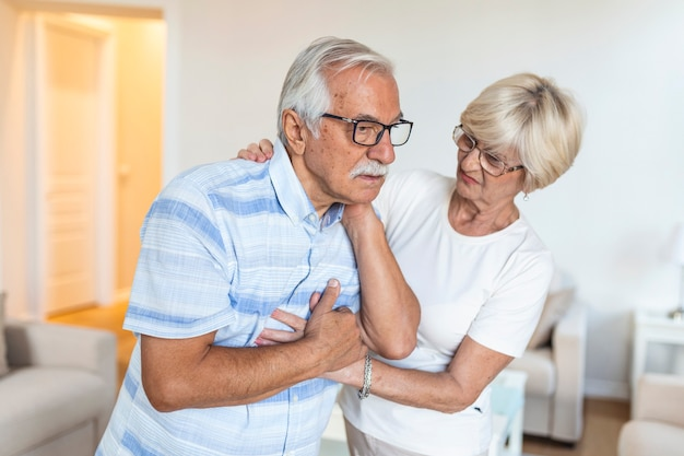 Senior man with neck pain and concerned elderly woman at home