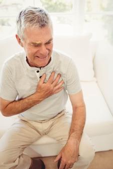 Старший мужчина с болью в сердце в спальне