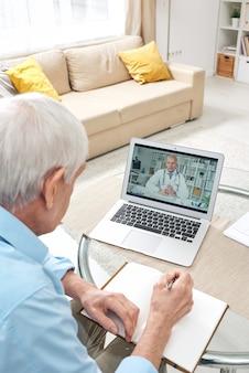 Старший мужчина с ручкой сидит за столом перед ноутбуком, смотрит онлайн-медицинскую консультацию и делает заметки в блокноте