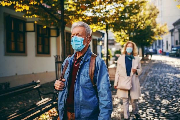 Senior man with a protective mask on, with backpack walking downtown on a sunny autumn day. in background is senior woman wearing mask, too.