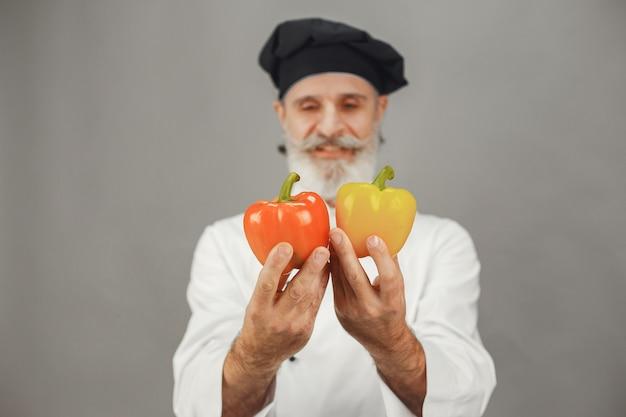 赤と黄色のコショウを持つ年配の男性。ビジネスへの専門的なアプローチ。