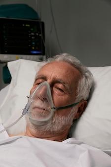 Uomo anziano con respiratore in un letto d'ospedale