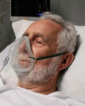 Старший мужчина с респиратором на больничной койке