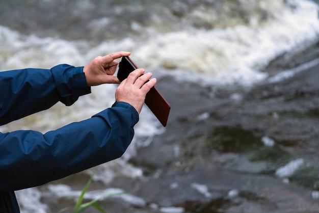 屋外で写真を撮るスマートフォンを持つ年配の男性。
