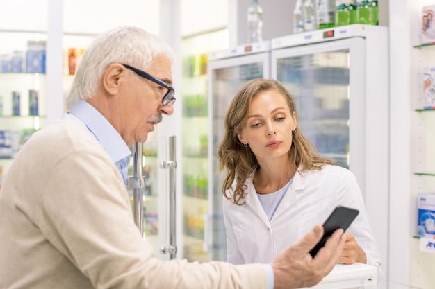 Старший мужчина со смартфоном показывает имя нового лекарства молодой женщине-консультанту в аптеке и спрашивает, есть ли оно у них