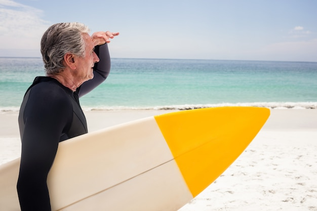Senior man with surfboard shielding eyes at beach
