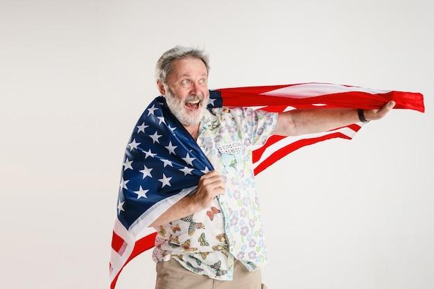 白いスタジオで隔離のアメリカ合衆国の旗を持つ年配の男性。