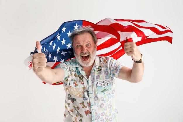 アメリカ合衆国の旗を持つシニア男性