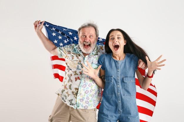 アメリカ合衆国の旗を持つ年配の男性