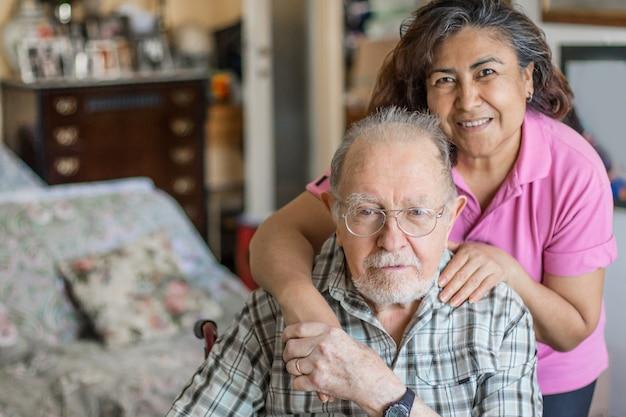 自宅で介護者と一緒に年配の男性。高齢者、障害者のためのヘルスケアの概念