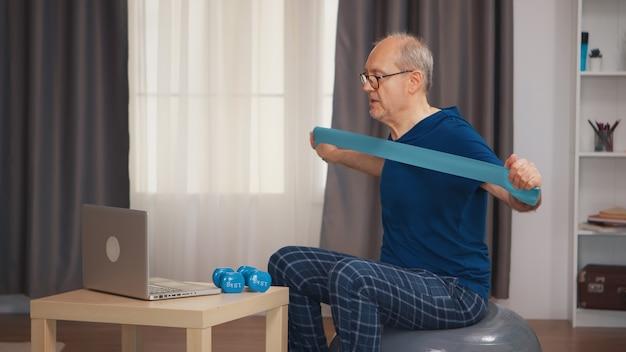 オンラインプログラムを見ているレジスタンスバンドでフィットネス運動をしている活力のある年配の男性。老人年金受給者が自宅でヘルスケアスポーツを健康的に訓練し、高齢者でフィットネス活動を行う