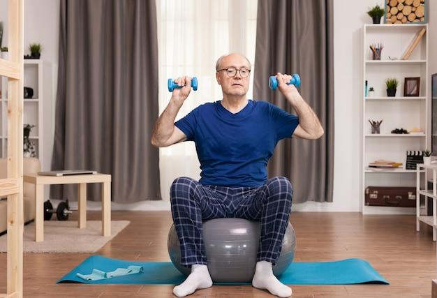 居間で運動する活力のある年配の男性。