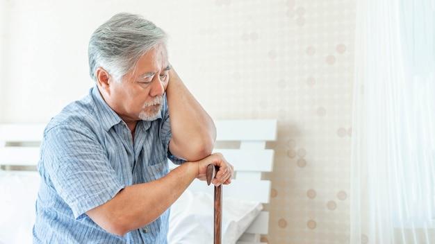 우울증으로 고통받는 침대에 앉아 지팡이를 짚고 있는 노인 - 노인은 상처와 외로운 문제를 겪고 있다