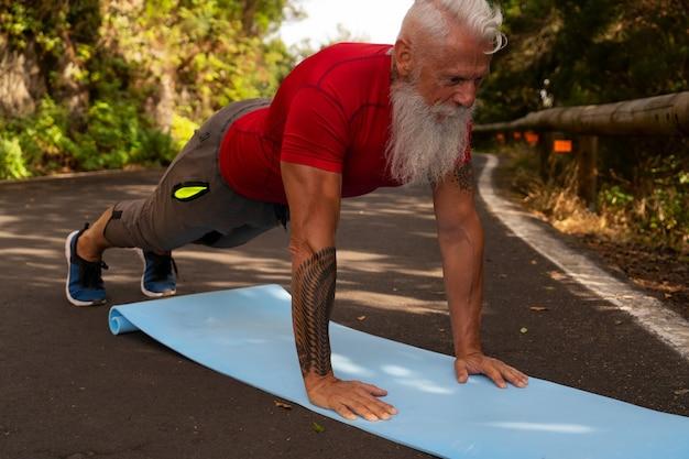 Старший мужчина с белой бородой делает упражнения на природе, подключается через ноутбук, новая концепция нормального и социального дистанцирования