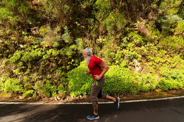 Старший мужчина с белой бородой занимается бегом на природе