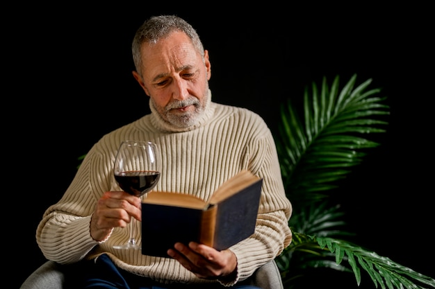 Senior man with wine reading near plant