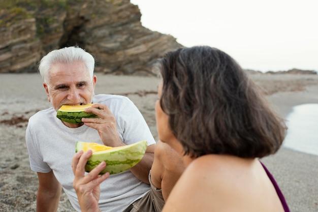 Senior man and woman eating watermelon at the beach