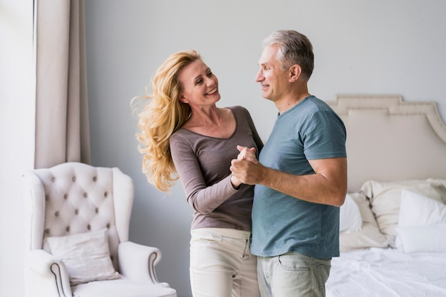Senior man and woman holding hands and smiling