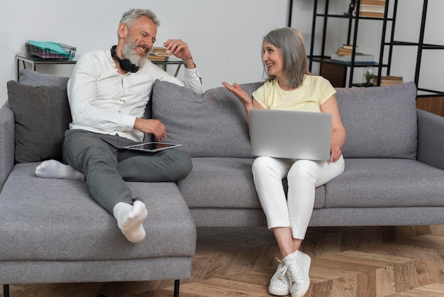 Senior man and woman at home on the couch using laptop and tablet