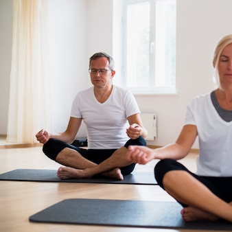 Senior man and woman meditating on yoga mats