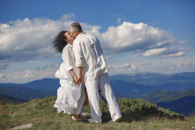 Senior uomo e donna in montagna. coppia adulta innamorata al tramonto. uomo in camicia bianca.