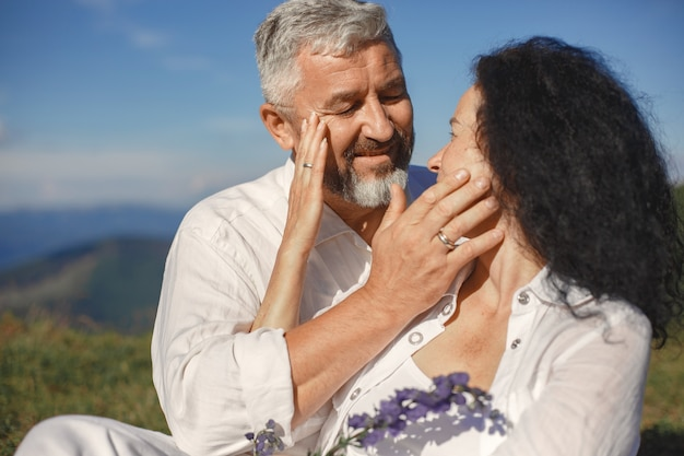 Senior man and woman in the mountains. adult couple in love at sunset. man in a white shirt.