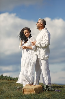 Senior man and woman in the mountains. woman with basket of flowers. man in a white shirt.