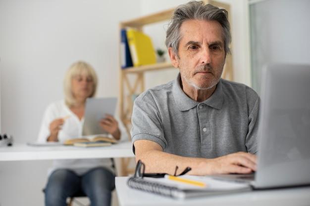 Uomo anziano e donna che prestano attenzione in classe