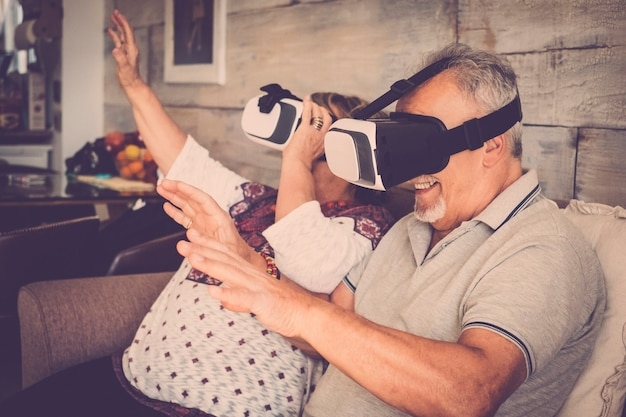 Senior man and woman with goggles headset virtual reality eyeglasses playing and have fun sitting on the sofa at home. warm filter and life together concept
