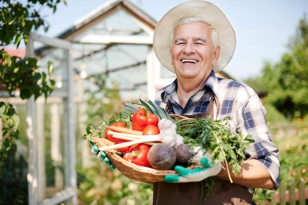 Uomo anziano che lavora nel campo con una cassa di verdure