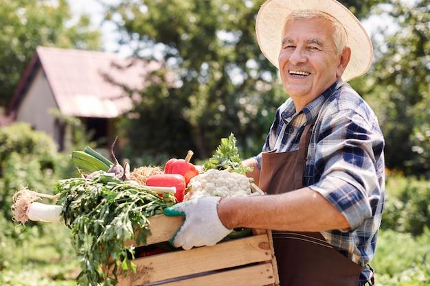 花とフィールドで働く年配の男性