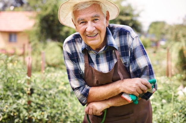 果物とフィールドで働く年配の男性